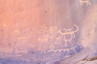 """Petroglyphs atop """"Una Vida. Two people, both with antennae, spirals but no spears or weapons, and lots of 4 leggeds just hanging out."""
